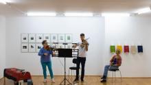 """Andrea Schumacher (Violine), Viktor Stenhjem (Violine) und Ulrike Knobloch-Sandhäger (Violine) proben in der Ausstellung """"Von Ferne - Bilder zur DDR""""  © Florian Ganslmeier"""