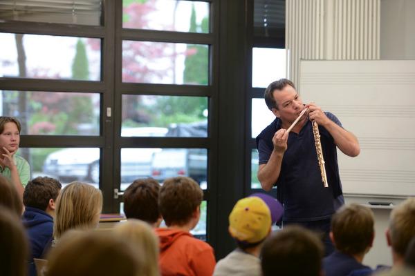Flötist Emanuel Pahud führt Kinder an sein Instrument heran